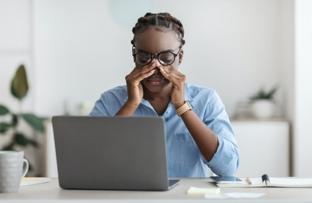 Eye Strain. Tired African Female Office Worker Sitting At Workplace Massaging Nosebridge